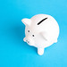 White piggy bank on blue background