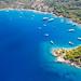 Luftbild von Luxusyachten im blauen Meer am Ekklisia Analipsi Strand auf Spetses und der Agios Georgios Kirche
