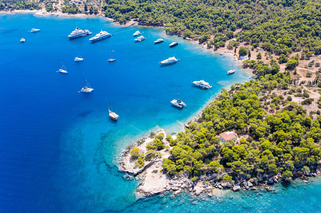 Aerial view of Catamarans and expensive ships In the blue bay at Ekklisia Analipsi of Spetses, next to Agios Georgios Church