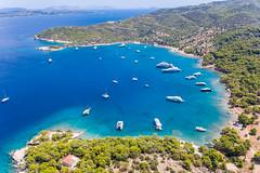Luftaufnahme zeigt Katamarane und teure Boote in der Bucht am Ekklisia Analipsi Küste der griechischen Insel Spetses