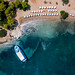 Aerial picture of a a ferry boat that docks in the argolic gulf, next to tourists at Zogeria Beach, Spetses