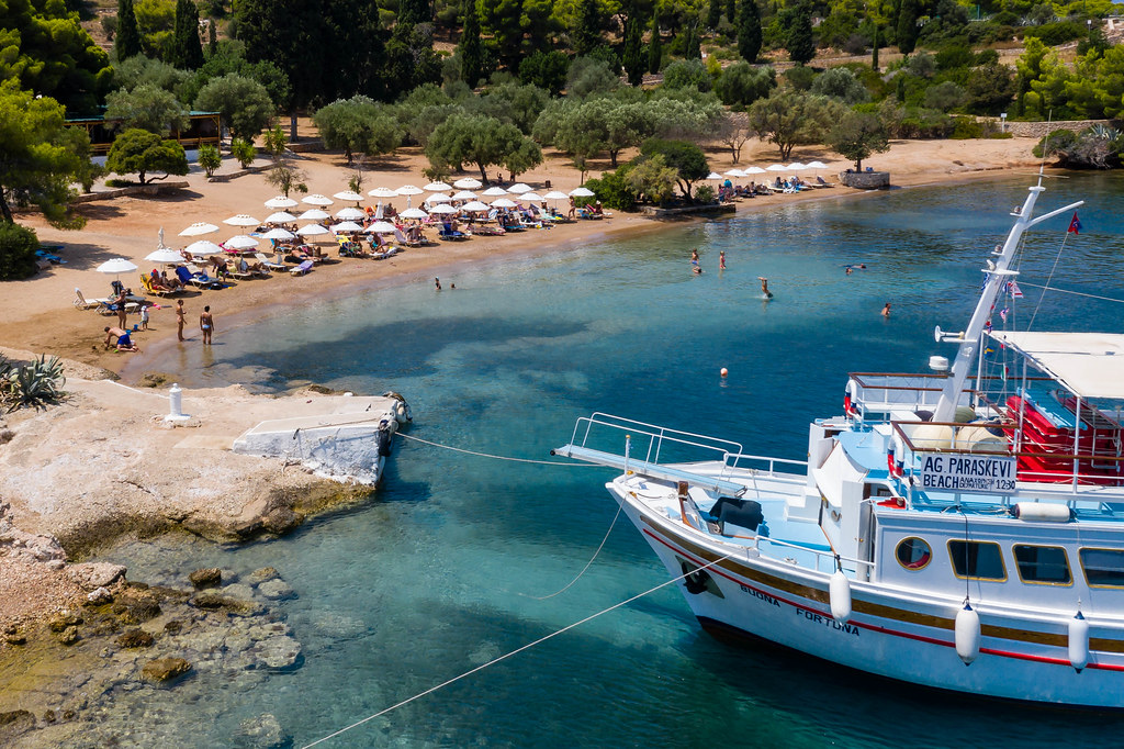 Aerial view shows the anchorage of a ferry at the island Spetses, with tourists swimming in the argolic gulf, in front of the green pine forest