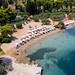 Luftbild des weißen Sandstrands mit Sonnenschirmen und Strandliegen, vor der Zogeria Strandbar auf Spetses, Griechenland