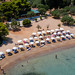 Aerial view of the white sandy beach with sunshades and beach chairs, in front of the Zogeria restaurant & beach bar on Spetses, Greece