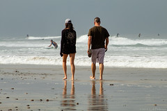 Couple Time (GoodLifeErik) Tags: morning pacificphotographicsociety encinitas california moonlightstatebeach outside ocean water pacificocean waves surfers telephoto reflections beach walking barefoot sand surf sunlight
