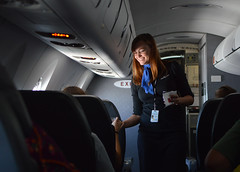 Service with a smile (radargeek) Tags: airplane flying flight attendant beverage smile firstclass americanairlines