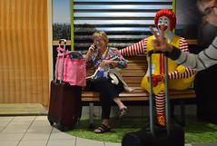Unexpected moments (radargeek) Tags: btv burlington airport kid child children kids traveler travelers traveling ronaldmcdonald photobomb bench cellphone vt vermont peace sign