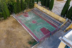 Aerial view shows two children on an old basketball court at Ligoneri Beach at Spetses, Greece