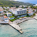 Aerial view of the shore of Spetses, Greece, with an hotel, aristocratic houses and Kaiki Beach at the green sea