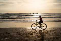 Biking on the Beach (Wits End Photography) Tags: ocean road street light shadow sea people reflection beach water bicycle silhouette backlight boats drive seaside sand costarica pavement streetphotography places route coastal shore tamarindo coastline form backlit nautical outline shape seashore roadway