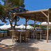 Restaurant porch by the sea in Argolis, Greece, with tables under a bast pavilion