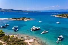Luftbild von teuren Yachten und Urlaubern auf Motorsportbooten im blauen Meer des Argolischen Golfs vor Ermionida, Griechenland