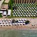 Luftbild von Urlaubern unter aufgereihten, weißen Sonnenschirmen am Strand von Chinitsa, Griechenland