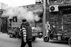 Fire in the hole (Go-tea 郭天) Tags: old winter shadow sun cold building history construction ancient alley pavement traditional bricks beijing sunny historic historical hutong tradition narrow pékin républiquepopulairedechine china street door city light people urban blackandwhite bw white man black window monochrome canon asian outside eos prime blackwhite back asia alone open natural outdoor candid tricycle smoke chinese naturallight motorbike motorcycle lonely backside 24mm bnw opened 100d
