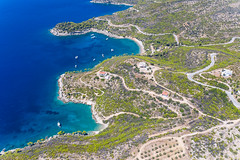 Aerial picture of single houses on the greek island Spetses, with its rocky coasts and boats on the blue sea