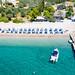 Luftbild zeigt ordentlich aufgestellte Sonnenschirme in blau und weiß, am Sandstrand von Agii Anargiri  und ein Motorsportboot auf dem klaren grünen Meer