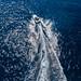 Luftbild zeigt einen Mann beim Wasserskifahren, auf dem dunkelblauen Meer