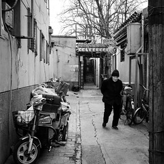 Back to black (Go-tea 郭天) Tags: pékin républiquepopulairedechine beijing hutong narrow alley ancient old traditional tradition history historical historic construction building bricks pavement cold winter sun sunny shadow portrait woman lady alone lonely wrinkles door walk walking bicycle bike motorbike motorcycle street urban city outside outdoor people candid bw bnw black white blackwhite blackandwhite naturallight natural light asia asian china chinese shandong canon eos 100d 24mm prime hat cap