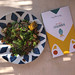 Top view of a colorful menu of Beach Project Restaurant in Greece, next to the meatless healthy meal Veggie Bowl with greens, corncobs & nuts