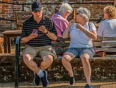 One ice cream is never enough.... (+Pattycake+) Tags: ©patriciawilden2019 people ranworthbroad opportunistshot bench evening norfolkuk candid eos70d eastanglia atmosphere shorts summer holidaymakers tourists sunshine street ranworth icecream knees