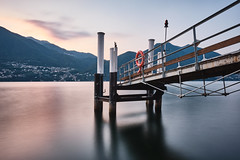 Brienno ferry stop 1 (PascallacsaP) Tags: lagodicomo lario lombardia lombardy como lago lake water shore mountains mountainlake village italia italy alps lakecomo longexposure ndfilter breakthroughfilters breakthroughphotography hills poles ferrystop ferry footbridge lifebuoy serene serenity dawn earlymorning pier comolake jetty 10stop 10stopndfilter