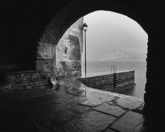 Brienno after a thunderstorm 2 (PascallacsaP) Tags: lagodicomo lario lombardia lombardy como lago lake water shore mountains mountainlake village italia italy alps quay lantern stairs ladder walls old stones pavement arch foggy rain rainy mist misty humid thunderstorm badweather longexposure ndfilter breakthroughphotography breakthroughfilters brienno brien lakecomo waterfront blackandwhite monochrome bw dawn earlymorning grey gray street ancient comolake wet fog 10stop 10stopndfilter