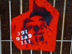 Not Dead Yet (Steve Taylor (Photography)) Tags: notdeadyet head face graffiti stencil streetart fence brown grey red white blue crazy strange uk gb england greatbritain unitedkingdom london