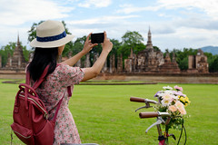 DAN_3853 (Mangpink) Tags: tourist woman one blackhair bag walking hat sukhothaihistoricalpark grassfields green ride bicycle flower taking photo phone architecture asia asian unesco tourism wat historical temple travel buddhist culture religion pagoda ancient sky landmark thailand building old buddha heritage palace famous park capital clouds statue destination exterior traditional structure stone ruins blue