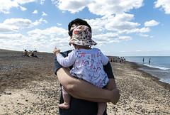 Fatherhood, Cley Beach, Norfolk (Bryan Appleyard) Tags: cley norfolk colour beach baby father d850 nikon 24120 clouds sea shingle bathers swimmers