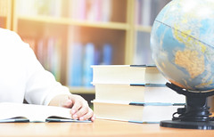 Education concept back to school and business study global world - Young woman student campus reading a book in library with book stacked and earth globe model map (poringdown) Tags: library book education background study stack literature school shelf university knowledge bookshelf learning concept wisdom history back literary college vintage paper group bookcase read information collection page textbook text research row ancient cover desk room student pile object young woman person girl pretty female adult holding lifestyle home portrait caucasian
