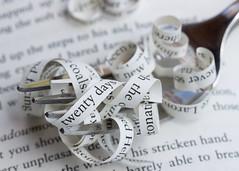 Eating One's Words (Helen Orozco) Tags: macromondays printedword hmm dessertfork book words paperstrips macro text twentydays papercurls fork forkful