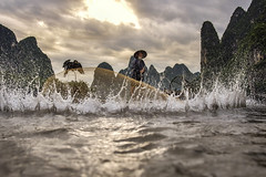 Cormorant fisherman throws a net with ancient bamboo boats at sunrise.Cormorant fisherman throws a net with ancient bamboo boats at sunrise. (VietNamBeautiful) Tags: fishing china bamboo fisherman cormorant traditional chinese net nature river boat person water travel xingping asia mountain bird ecology morning scenery tradition guy village elderly dawn background fisher ecotourism sunrise beautiful silhouette portrait animal environment night clothing sunset working stick karst yangshuo guangxi guizhou li guilin ancient hills tilt shift