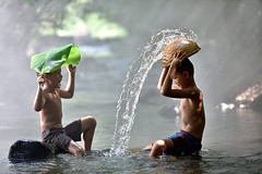 Two boys playing in a river in Thailand.Two boys playing in a river in Thailand. (Wonderful Vietnam) Tags: childrens water playing vietnam river kid indonesia funny lifestyle malaysia child cambodia thailand poor myanmar people splash happy rural person summer enthusiasm caucasian cute fresh fun boy space outdoor happiness kids sport joy sun vacation expression play two asian standing face recreation active wet sunset strength rustic laugh summertime fantastic