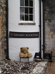 The Bookseller (catrionatv) Tags: hampshire winchester cathedral innerclose deanerybookstall gravel wall flintwall window windowframe windowsill drainpipes sign chairs teddybear bookseller