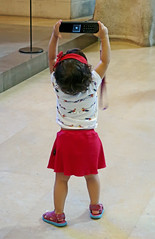Great form as a photographer (except she's 'shooting' with the audio guide from the tour) - Sagrada Familia, Barcelona, Spain (TravelsWithDan) Tags: toddler younggirl candid photographer audioguide sagradafamilia cathedral greatform theotherphotographer church city urban barcelona spain europe canong9x catalonia