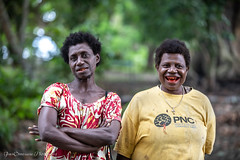 Women with betel nut smile, Mioko Island, Papua New Guinea, July 2019. Chewing a betel nut produces red residue and acts as a mild stimulant. (Catherine Gidzinska and Simon Gidzinski) Tags: 2019 eastnewbritain island mioko miokoisland png papuanewguinea adventure betel betelnut colour colourful gidzinska gidzinski grainconnoisseur green grethigh high indigenous islanders jungle palm peaceful remote village woman women red smile ngc portrait tribe tribalwoman tribal papua