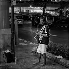 Blues in the night (John Riper) Tags: bangkok street bw white black monochrome john square photography mono zwartwit candid fujifilm vierkant xt3 straatfotografie riper johnriper musician night thailand blues barefoot sax saxophone