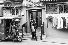 Ready for departure (Go-tea 郭天) Tags: pékin républiquepopulairedechine beijing hutong narrow alley old ancient history historical historic traditional tradition building construction bricks pavement cold winter sun sunny shadow man woman hat cap motorcycle motorbike tricycle departure ready preparation preparing laundry clothes door open bag 2 together transportation transport busy trip street urban city outside outdoor people candid bw bnw black white blackwhite blackandwhite monochrome naturallight natural light asia asian china chinese canon eos 100d 24mm prime