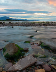 Beach Sunset number 2 (ivanstevensphotography) Tags: sea seaweed rocks pebbles river sunset clouds colour mountains scenery landscape seascape