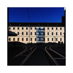 glimmering rails (Armin Fuchs) Tags: arminfuchs lavillelaplusdangereuse würzburg juliusspital constructionsite blue sky yellow building hospital rails people light shadow perspective 24mm square