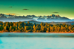 Dramatic light on the Peaks of the Southern Alps behind the forest and Okarito Lagoon (stewart.watsonnz) Tags: lake water mountain tree nature landscape sky sunset outdoors plant reflection mountainrange wilderness coast cloud summer naturallandscape outdoor bodyofwater noperson travel background scenery mountainouslandforms shoreline large green scenic blue dawn land waterresources wood colorful panoramic vegetation alps yellow nationalpark shore lagoon mountscenery ocean calm field bank sunlight evening sunrise horizon
