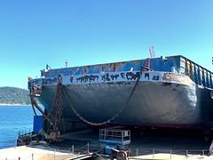 Barge Refurbishing Progress (DanaStyber) Tags: paintandbodywork drydock barge dci anacorteswa industrialphotography orangeandblue chainlink portofanacortes boats