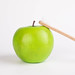 Green apple with wooden toothbrush