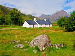 Black Rock Cottage (lesleydugmore) Tags: scotland britain europe uk westhighlands glencoe cottage blackrockcottage highlands grass green white red mountains sky clouds blue trees rock