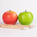 Red and green apple with wooden toothbrushes on white background