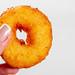 Little fried donut in hand in woman