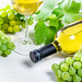 Bottle of white wine, glass, green grapes and leaves on white table