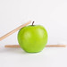 Green apple with wooden toothbrushes on white background