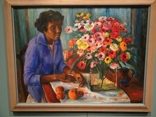 Brisbane. One of Margaraet Olley's still lifes of  anenomes and peaches with a young  Aboriginal  woman. Part of the Margaret Olley a Generous Life exhibition at the Brisbane Gallery of Modern Art in 2019.