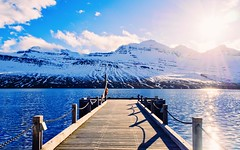 Dock (Caleb Bertolini) Tags: olympus nature water fjord town mountain snow winter sky clouds lake blue white landscape iceland mirrorless mountains home beach rocks peaks ocean natural scenery range outside boat boats sun sunset flare
